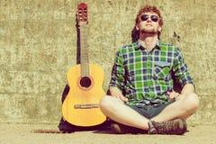 Hombre barbudo joven del inconformista con la guitarra al aire libre Imagen de archivo libre de regalías