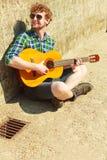 Hombre barbudo joven del inconformista con la guitarra al aire libre Fotografía de archivo libre de regalías
