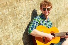 Hombre barbudo joven del inconformista con la guitarra al aire libre Fotografía de archivo