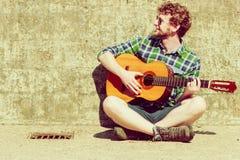 Hombre barbudo joven del inconformista con la guitarra al aire libre Imagenes de archivo