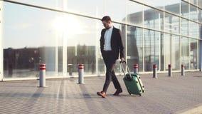 Hombre barbudo joven elegante en las gafas de sol que salen el terminal de aeropuerto con equipaje, respuestas el teléfono Estilo almacen de metraje de vídeo