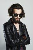 Hombre barbudo joven en cuero Inconformista en gafas de sol Fotos de archivo