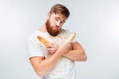 Hombre barbudo joven en la camisa asquerosa que sostiene dos perritos calientes Imagen de archivo libre de regalías