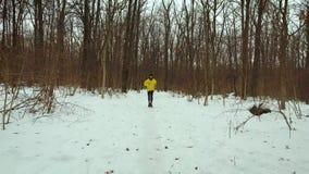 Hombre barbudo joven en la capa amarilla que corre en bosque en día de invierno frío almacen de video