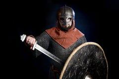 Hombre barbudo joven en un casco de la Viking-era que cubre su cara que sostiene una espada y un escudo imagen de archivo libre de regalías