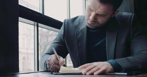 Hombre barbudo joven en un equipo formal que anota las ideas en el papel en un café Siendo el jefe acertado almacen de video