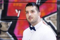 Hombre barbudo joven hermoso con la camisa y la corbata de lazo blancas en la calle Imagen de archivo