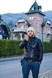 Hombre barbudo joven que envía besos en fondo de la casa rosada vieja hermosa en la montaña Fotografía de archivo libre de regalías