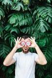 Hombre barbudo joven que lleva a cabo las rebanadas de fruta del drag?n de Pitaya delante de sus ojos, sorprendidas fotos de archivo libres de regalías