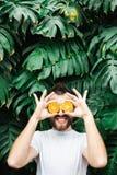 Hombre barbudo joven que lleva a cabo las rebanadas de mandarina anaranjada delante de sus ojos, riendo imágenes de archivo libres de regalías