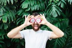 Hombre barbudo joven que lleva a cabo rebanadas de fruta delante de sus ojos, lengua del dragón de Pitaya hacia fuera foto de archivo