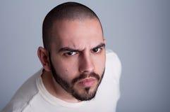 Hombre barbudo joven que parece enojado Foto de archivo