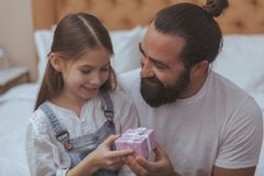 Hombre barbudo maduro que descansa en casa con su pequeña hija fotos de archivo libres de regalías