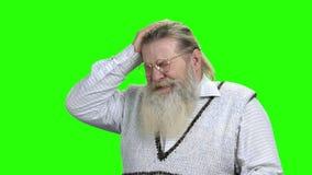 Hombre barbudo mayor que tiene dolor de cabeza severo almacen de metraje de vídeo