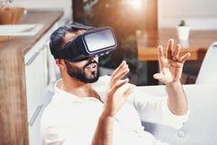 Hombre barbudo multicultural que usa gafas de la realidad virtual imágenes de archivo libres de regalías