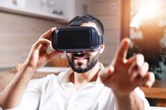 Hombre barbudo multicultural que usa gafas de la realidad virtual fotos de archivo