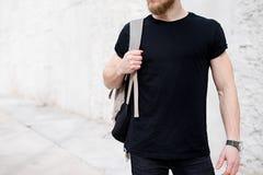 Hombre barbudo muscular joven que lleva la camiseta negra y la mochila que presentan afuera Muro de cemento blanco vacío en el fo fotos de archivo