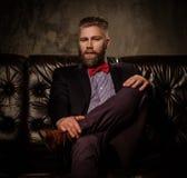Hombre barbudo pasado de moda que se sienta en el sofá de cuero cómodo aislado en gris Fotos de archivo libres de regalías