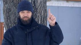 Hombre barbudo pobre en los auriculares que llevan de un día de invierno que muestran su dedo índice para arriba almacen de metraje de vídeo