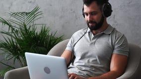 Hombre barbudo positivo que trabaja en el ordenador portátil metrajes