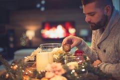 Hombre barbudo que adorna la tabla de la Navidad Foto de archivo libre de regalías