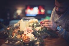 Hombre barbudo que adorna la tabla de la Navidad Foto de archivo
