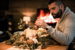 Hombre barbudo que adorna la tabla de la Navidad Imagen de archivo libre de regalías