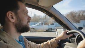 Hombre barbudo que conduce un coche en un d?a soleado en la ciudad almacen de video