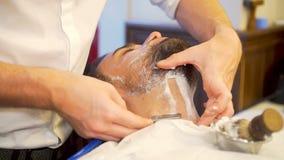 Hombre barbudo que consigue corte de pelo de la barba y afeitado almacen de video