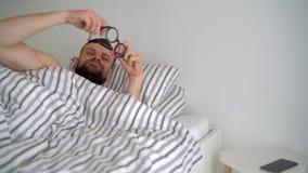 Hombre barbudo que despierta en cama debajo de la manta, sonriendo, poniendo sus lentes y tomando su smartphonephone