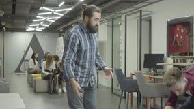 Hombre barbudo que estudia los papeles en la oficina Colega joven que monta la bici en la oficina y al individuo barbudo de los e almacen de video