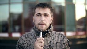 Hombre barbudo que fuma el cigarrillo electrónico almacen de metraje de vídeo