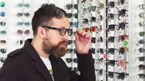 Hombre barbudo que intenta sobre los vidrios en la tienda de las gafas almacen de metraje de vídeo