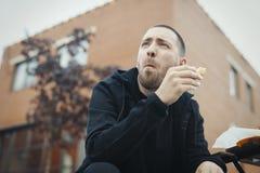 Hombre barbudo que mastica el bocadillo en la calle fotografía de archivo