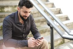 Hombre barbudo que mira smartphone en escaleras fotografía de archivo