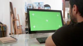 Hombre barbudo que mira una pantalla verde en su ordenador metrajes