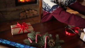Hombre barbudo que sienta y que ata un arco en regalos por Año Nuevo cerca de la chimenea Sombrero de la Navidad del individuo qu metrajes