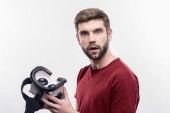 Hombre barbudo que siente excitado sosteniendo los vidrios de la realidad virtual por primera vez fotos de archivo