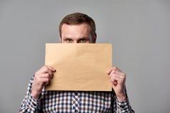 Hombre barbudo que sostiene el sobre marrón en blanco imagen de archivo