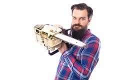 Hombre barbudo que sostiene una motosierra aislada en un fondo blanco fotos de archivo libres de regalías