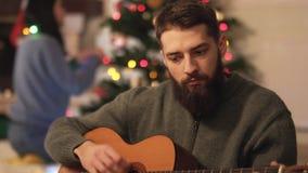 Hombre barbudo que toca la guitarra y que canta la sentada en el piso cerca del árbol de navidad Los pares felices se preparan pa almacen de metraje de vídeo