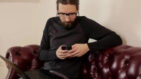 Hombre barbudo que trabaja con el ordenador portátil y el smartphone metrajes