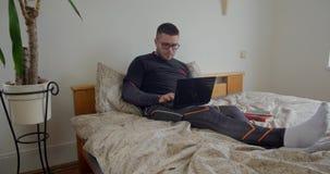 Hombre barbudo que trabaja en el dormitorio con el ordenador portátil almacen de metraje de vídeo