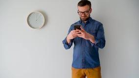 Hombre barbudo que usa smartphone contra una pared gris con un reloj almacen de video