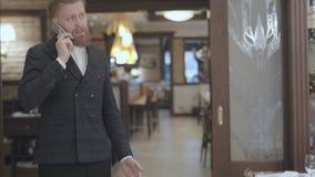Hombre barbudo rubio confiado en chaqueta elegante que habla por la situación del teléfono móvil en restaurante moderno El hombre almacen de metraje de vídeo