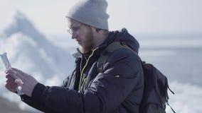Hombre barbudo rubio hermoso en vidrios con la mochila que comprueba el mapa delante del hielo en el del norte o South Pole Turis almacen de video