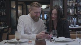 Hombre barbudo rubio y mujer morena bonita que se sientan en el restaurante en la tabla El hombre muestra a su novia metrajes