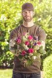 Hombre barbudo 20s que sostiene el manojo de flores Imágenes de archivo libres de regalías