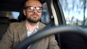 Hombre barbudo satisfecho en los vidrios que conducen un coche abajo de la calle en tiempo soleado almacen de video