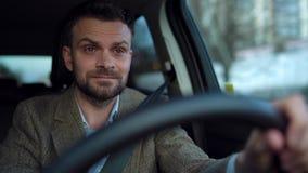 Hombre barbudo satisfecho que conduce un coche abajo de la calle en tiempo soleado metrajes